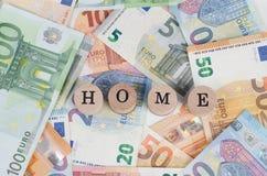 Euro billets de banque avec la maison d'adresse dans le premier plan photographie stock