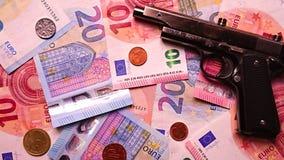 Euro billets de banque avec une arme à feu photographie stock