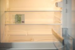 Euro billets de banque dans un réfrigérateur vide : une poignée de 100 billets de banque d'euros dans un réfrigérateur vide Argen Photos libres de droits