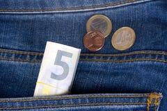 Euro billets de banque et pièces de monnaie sur la poche Images libres de droits