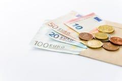 Euro billets de banque et pièces de monnaie sur le fond blanc Image libre de droits