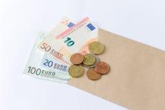 Euro billets de banque et pièces de monnaie sur le fond blanc Images stock