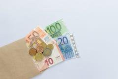 Euro billets de banque et pièces de monnaie sur le fond blanc Photos stock