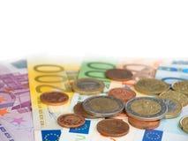 Euro billets de banque et pile de pièces de monnaie d'isolement sur le blanc Photographie stock