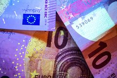 Euro billets de banque illuminés avec la lumière UV Photos stock
