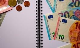 Euro billets de banque, pièces de monnaie sur un bloc-notes blanc photos libres de droits