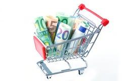 Euro billets de banque roulés dans le chariot de supermarché Image libre de droits