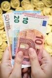 Euro billets en main avec des pièces d'or Photo stock