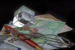 Euro billets, pièces, stylo, et verres sur le fond noir Images stock