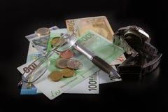 Euro billets, pièces, stylo, verres et montre sur le fond noir Image libre de droits