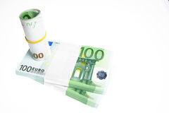 Euro Bills. A stack and a roll of 100 Euro bills isolated on white background Stock Image