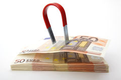 Euro bills attracted by a magnet. On white background Stock Photo