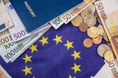 Euro bills with coin, passport above flag Stock Photos
