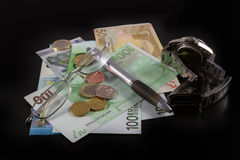 Euro bills, Coins, Pen, Glasses and Watch on black background Royalty Free Stock Image