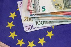 Euro bills with euro flag. On desk Stock Photos