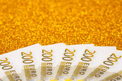 200 euro bills on golden sparkling background. A lot of money, luxury Stock Photo