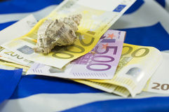 Euro bills on the Greek flag with the shell on top. Euro bills on the Greek flag and the shell on top, with low depth of field. Tourism income abstract royalty free stock photos