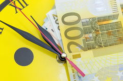 Euro bills on top of the clock Stock Photos