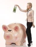 Euro biondo piacevole di risparmio della donna in un grande salvadanaio di porcellino Immagini Stock Libere da Diritti