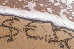 Euro, Bitcoin et symboles dollar écrits dans le sable de mer Les vagues ont enlevé l'inscription images libres de droits