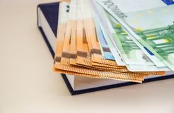 Euro on the book on the background of a wooden table. Money on the book on the background of a wooden table stock photo