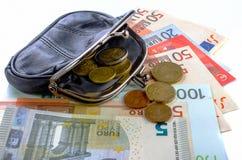 Euro in borsa nera e monete su un fondo bianco Fotografie Stock