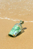 100 euro in a bottle on the beach Stock Photo