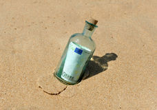 100 euro in a bottle on the sand Stock Photos