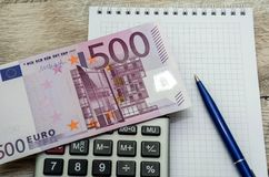 500 euro, calculator, notebook and pen close-up stock photography