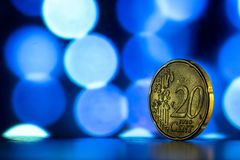 Yellow coin on a background of blue bokeh Royalty Free Stock Image