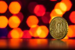 Yellow coin on a background of orange bokeh. Euro cent close up on a background of purple bokeh Stock Photo