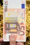 Euro cinquanta a disposizione con le monete di oro Fotografia Stock Libera da Diritti