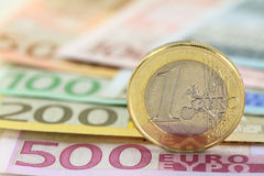 Euro coin. Against euro notes. Shallow DOF on coin Royalty Free Stock Images