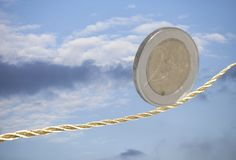 2 Euro coin balancing on golden rope Royalty Free Stock Image