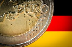 2 Euro coin with a blurred flag of Germany on the background.  royalty free stock photo