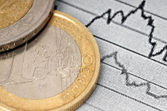 Euro coin and chart. Euro coin and financial graph on paper.Graphical representation of the movement of Finance Royalty Free Stock Images