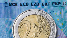 Euro coin close up on a twenty euro paper money Royalty Free Stock Photo