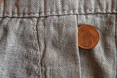 Euro coin with a denomination of 1 euro cent in the pocket of old linen pants. Euro coin with a denomination of one euro cent in the pocket of old linen pants Stock Photos