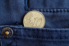 Euro coin with a denomination of 10 euro cents in the pocket of dark blue denim jeans.  Stock Photography