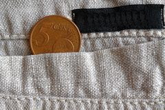 Euro coin with a denomination of five euro cents in the pocket of linen pants with black stripe. Euro coin with a denomination of 5 euro cents in the pocket of Royalty Free Stock Image