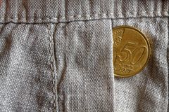 Euro coin with a denomination of 50 euro cents in the pocket of old linen pants Royalty Free Stock Photos