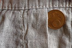 Euro coin with a denomination of 5 euro cents in the pocket of old linen pants. Euro coin with a denomination of five euro cents in the pocket of old linen pants Stock Photos