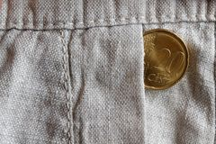 Euro coin with a denomination of 20 euro cents in the pocket of old linen pants. Euro coin with a denomination of twenty euro cents in the pocket of old linen Stock Photo