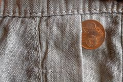 Euro coin with a denomination of 2 euro cents in the pocket of old linen pants. Euro coin with a denomination of two euro cents in the pocket of old linen pants Royalty Free Stock Images