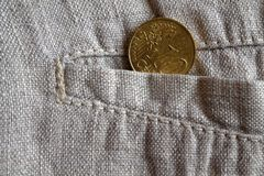 Euro coin with a denomination of 10 euro cents in the pocket of worn linen pants. Euro coin with a denomination of ten euro cents in the pocket of worn linen Stock Images