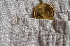 Euro coin with a denomination of 20 euro cents in the pocket of worn linen pants. Euro coin with a denomination of twenty euro cents in the pocket of worn linen Royalty Free Stock Images