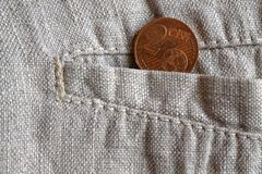 Euro coin with a denomination of 2 euro cents in the pocket of worn linen pants. Euro coin with a denomination of two euro cents in the pocket of worn linen Stock Photos