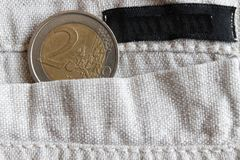 Euro coin with a denomination of two euro in the pocket of linen pants with black stripe. Euro coin with a denomination of 2 euro in the pocket of linen pants Stock Image