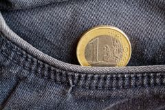 Euro coin with a denomination of one euro in the pocket of obsolete blue denim jeans. Euro coin with a denomination of 1 euro in the pocket of obsolete blue Royalty Free Stock Photos