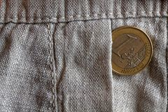 Euro coin with a denomination of one euro in the pocket of old linen pants Royalty Free Stock Photos